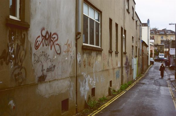 Colour view of Hampton Lane on an overcast day with grafitti and a woman in a long black coat in the middle distance