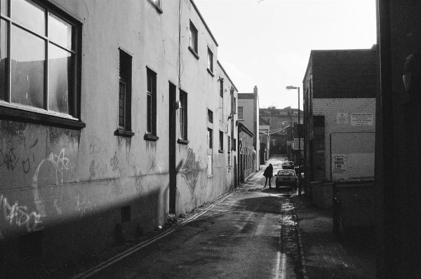 Black and white photo of Hampton lane on a sunny day with a lone sihouletted individual