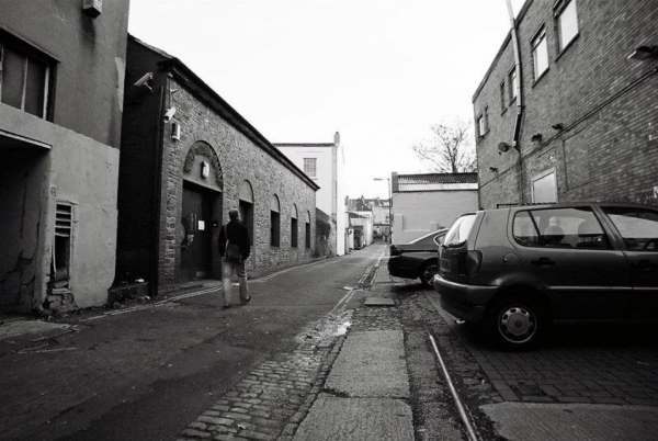 Black and white view of Hampton Lane from a low angle with a single individual in the forground