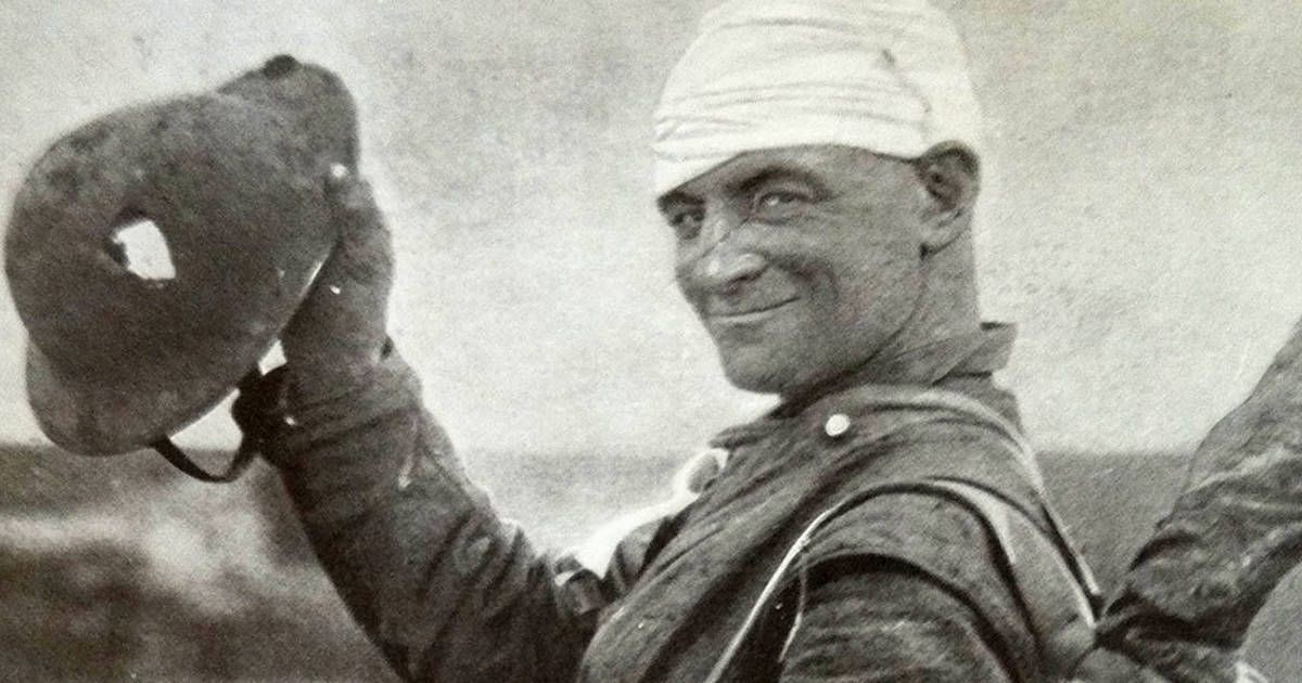 A smiling WWI british soldier with his head bandaged, brandishing his helmet with a large ragged hole in it